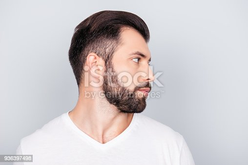 698023272 istock photo Advertising barbershop concept. Profile side portrait of handsome brunet bearded young man. He has a perfect stunning hair cut, in white t shirt isolated on light grey backgroung 936397498