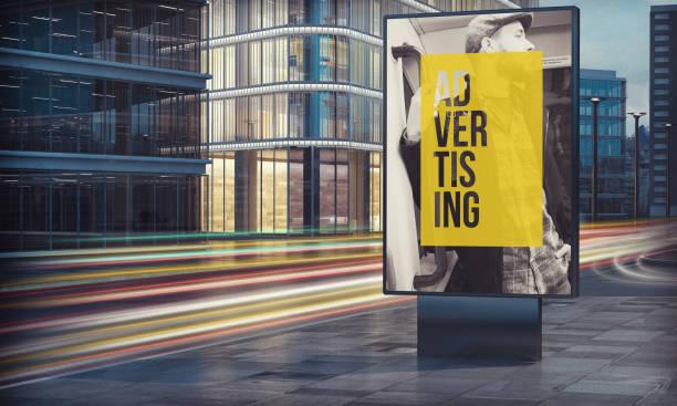 panneau d'affichage publicitaire dans la nuit de la ville - publicité photos et images de collection
