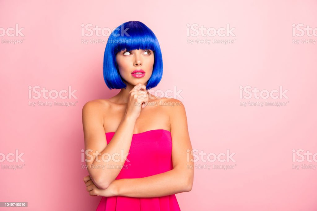 Advertising concept. Portrait dreamy lady in dress hold hand touch chin looking aside isolated on pastel pink background with copy space empty place for product stock photo