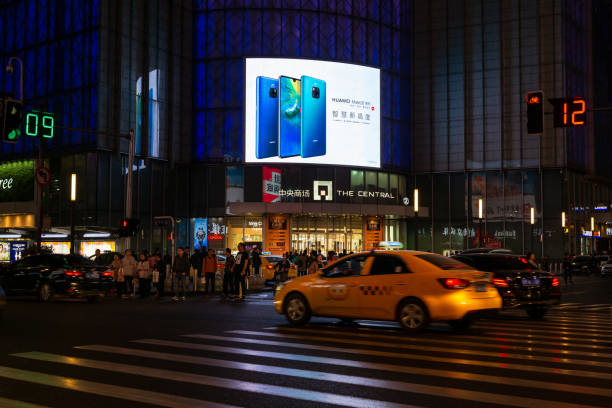 Advertising for huawei's new phones NanJing,JiangSu/China-October 31 2018:There are people and cars on the streets at night, and the store's LED display is advertising huawei's Mate20 new mobile phone huawei stock pictures, royalty-free photos & images