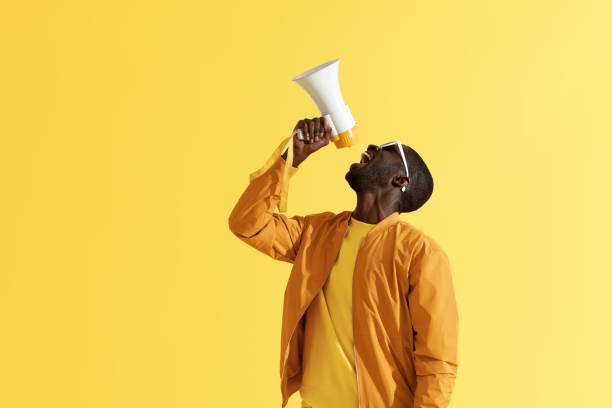 Advertising. Man screaming announcement in megaphone portrait Advertising. Man screaming announcement in megaphone on yellow background. Portrait of african american male model in fashion wear using loud speaker in studio toned image stock pictures, royalty-free photos & images