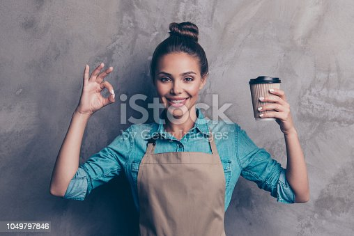 istock Advertising, pause, relax, rest concept.  Beautiful, attractive, pretty woman in denim jeans, with cup of coffee in hands showing OK sign isolated on gray textured wall background 1049797846