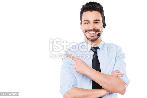 Handsome young male operator pointing away and smiling while standing against white background