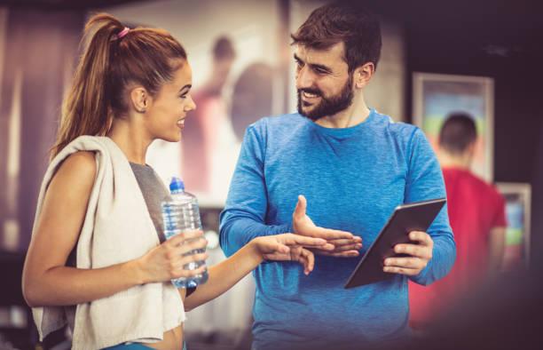 asesoramiento para el ejercicio. - entrenador personal fotografías e imágenes de stock