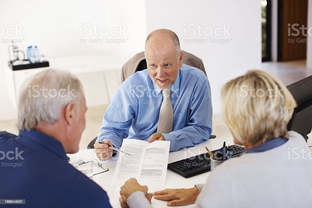 Advisor advising couple with financial papers royalty-free stock photo