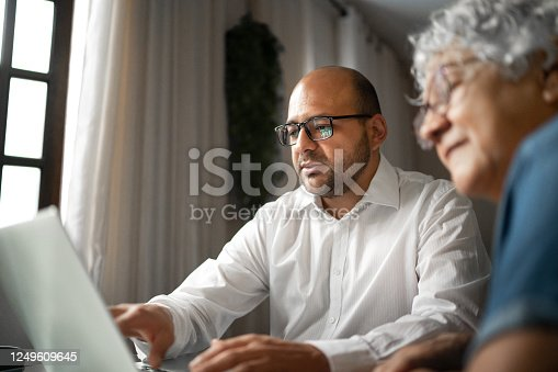 Advisor helping a senior woman at home (or mother and son)