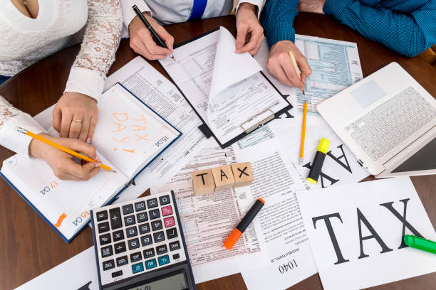 Advisors help in filling 1040 form, teamwork in office Advisors help in filling 1040 form, teamwork in office income tax stock pictures, royalty-free photos & images