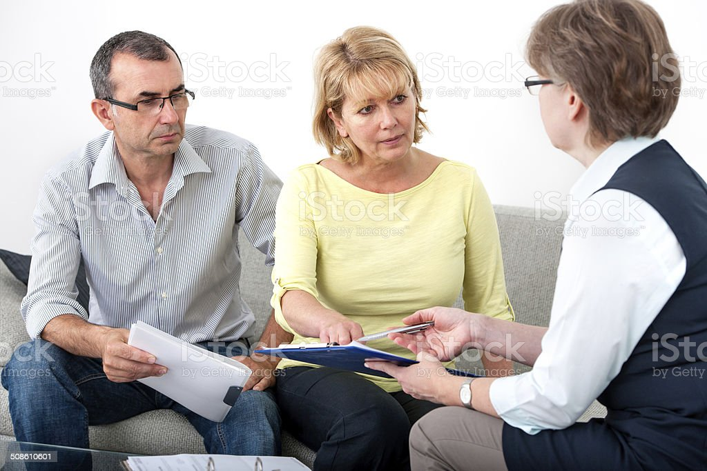 Advisory service for debtors Mature couple getting financial advice from consultant at home Active Seniors Stock Photo