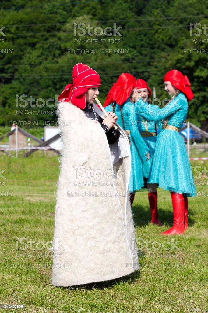 ADYGEA, RUSSIA - JULY 25 2015: Adyghe boy in Circassian national dress playing the flute in the background laughing girl, selective focus stock photo