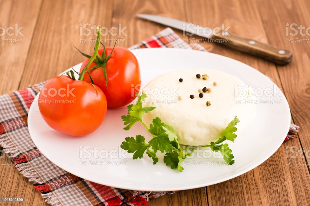 Adyghe cheese, tomato and parsley on a plate stock photo