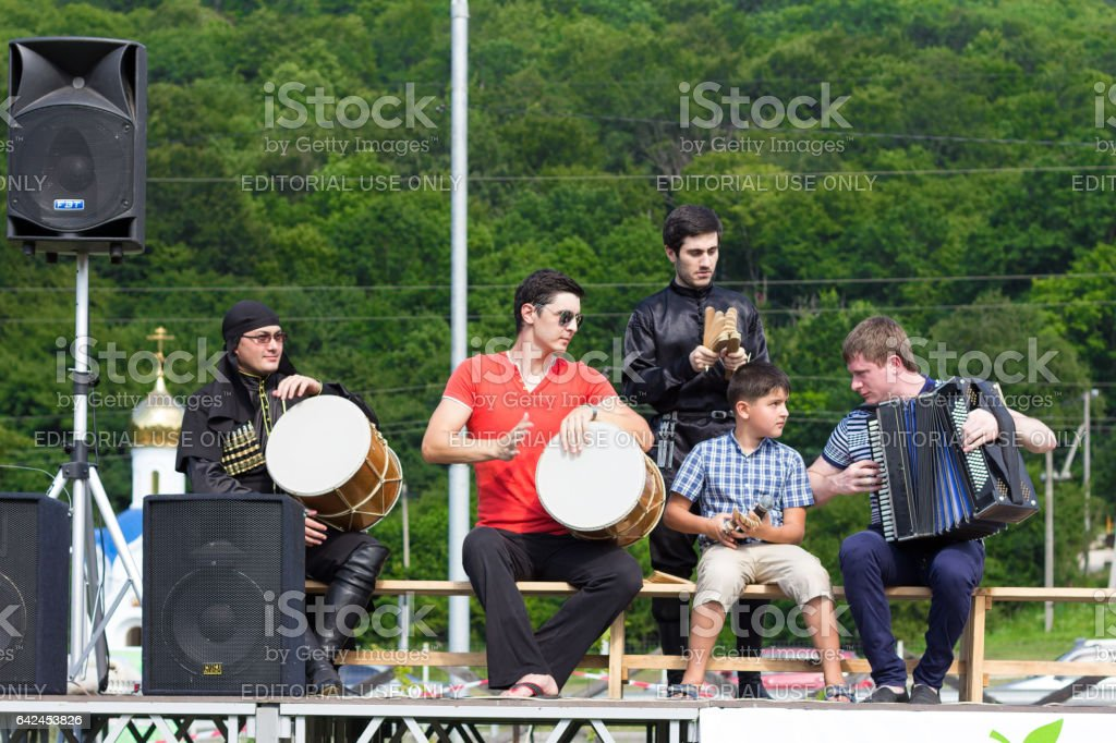 ADYGEA, RUSSIA - JULY 25 2015: Adyghe musical ensemble in the Circassian national costumes playing on stage on a background of green forest on ethnic festival in the mountains of Adygea stock photo