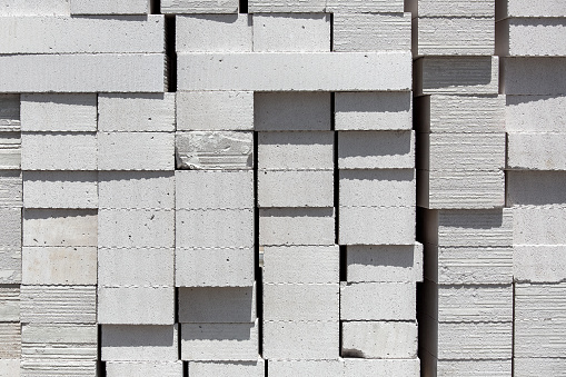 istock Aerated concrete blocks of light building material of white color piled on a pile for construction, texture closeup nobody. 1249197093
