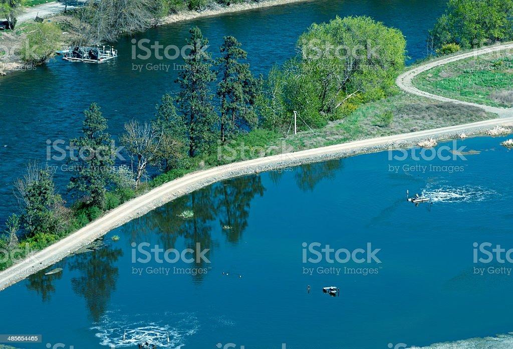 Aeration lagoon at sewage treatment plant by river stock photo