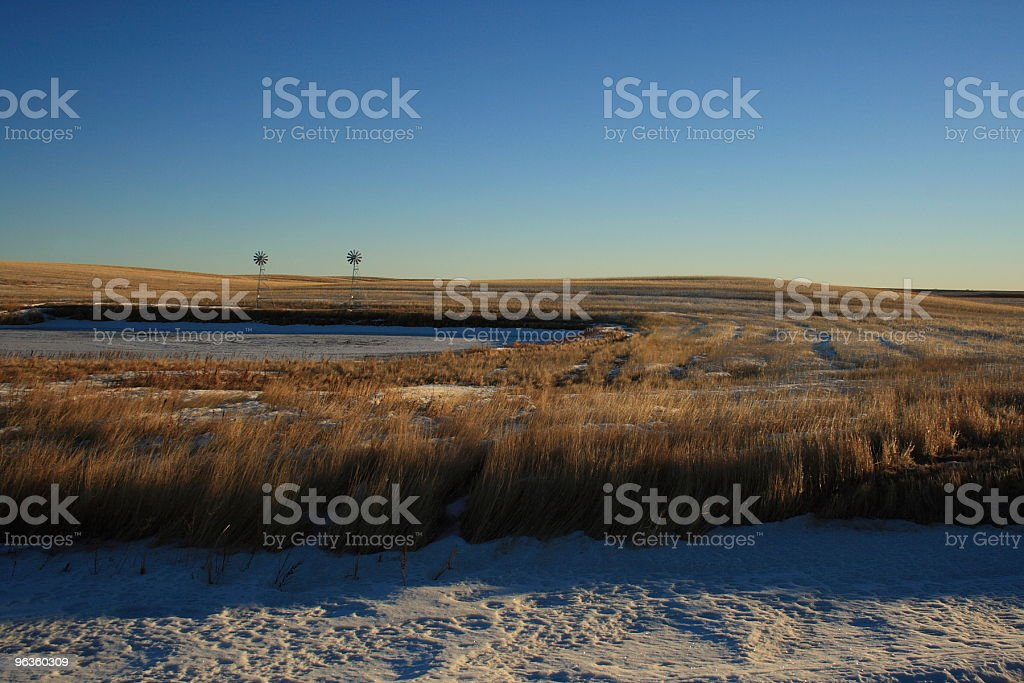 Aeration windmills at the edge of a fish pond royalty-free stock photo