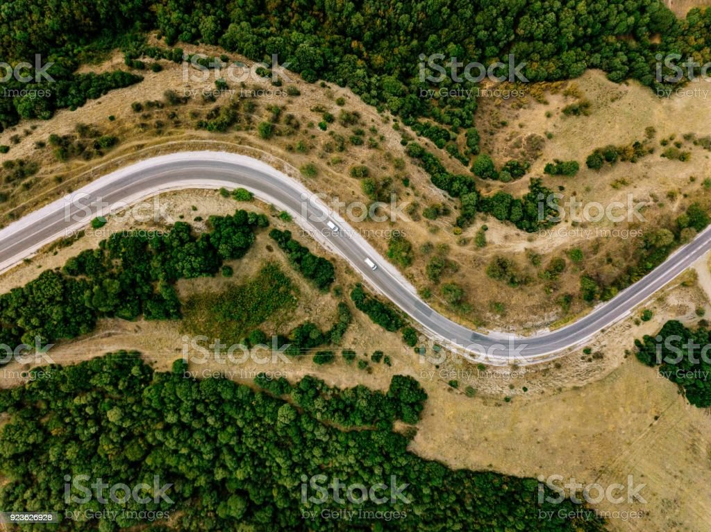 Aerial above view of a rural landscape with a curvy road running through it in Greece. stock photo