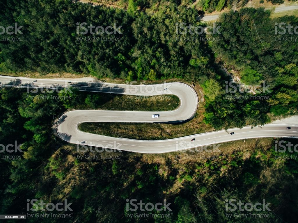 Aerial above view of a rural mountain landscape with a curvy road in...