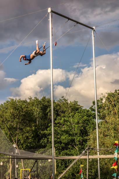 aerial acrobat am trapez im park - trapez stock-fotos und bilder