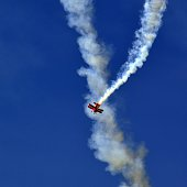 Small red airplane flying in a loop