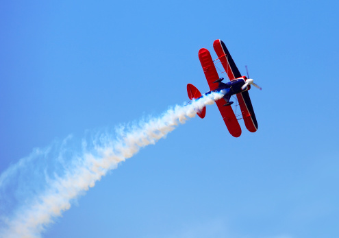Aerial acrobatics - red propeller plane with smoke trail against clear blue sky