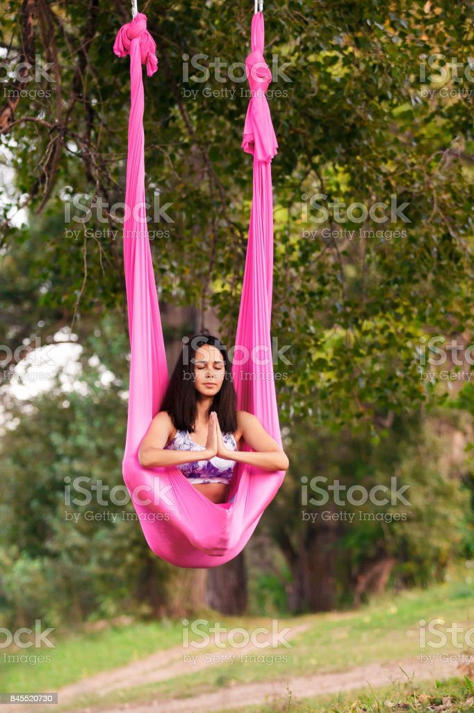Aerial antigravity yoga. Young healthy women doing lotus pose on silk hammock at nature stock photo