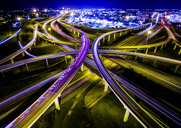 Aerial Austin Ambulance Interstate Interchange Expansive Night TimeLapse Aerial Ambulance Rushing Interstate Highway Interchange Night TimeLapse of Headlights and brake lights driving down the highway. The Crossover from 183 and Mopac Expressway. A long night shot in Austin Texas. Illuminated City lights. The Vast Expansive Never ending Fossil Fuel Using Energy Huge of A Civilization  overpass road stock pictures, royalty-free photos & images