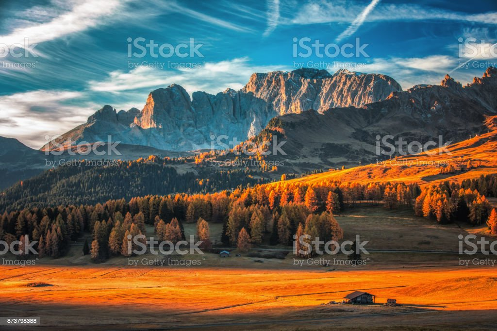 Aerial autumn sunrise scenery with yellow larches and small alpine building and Odle - Geisler mountain group on background. Alpe di Siusi (Seiser Alm), Dolomite Alps, Italy stock photo
