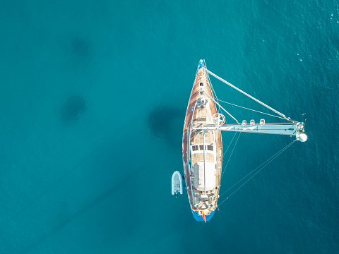 istock Aerial bird's eye view drone of boat docked in mediterranean tropical beach with turquoise - sapphire waters 1008244442