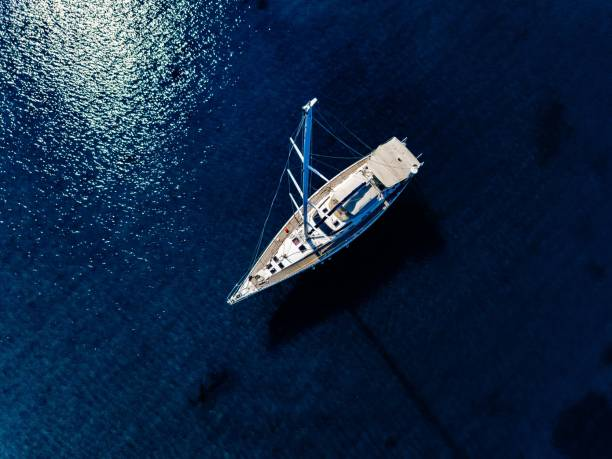 Aerial birds eye view from drone of yacht in deep blue sea stock photo