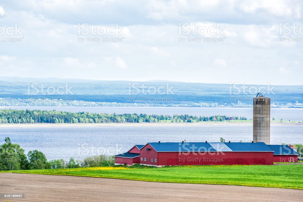 Aerial cityscape landscape view of farmland in Ile D'Orleans, Quebec, Canada, plowed field, furrows, farm and grain storage silo barn, shed or by Saint Lawrence river with hills, mountains and village stock photo