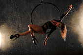 Aerial dancer during the rain. Young sports girl dancing with an air hoop. She is dressed in a black dress and high heels. Aerial dancer performance with ring.