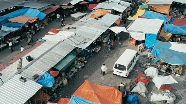 luftbild-drohne bild der stadt von morgen zu vermarkten, mit bunten zelten auf der suche nach unten nahaufnahme beim menschen herumlaufen - plane kaufen stock-fotos und bilder