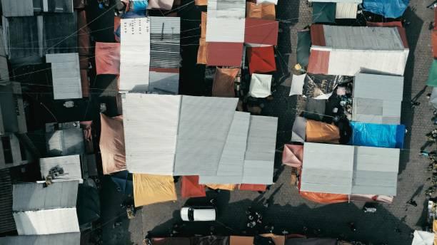 luftbild-drohne bild der stadt von morgen zu vermarkten, mit bunten zelten, die auf der suche nach unten - plane kaufen stock-fotos und bilder