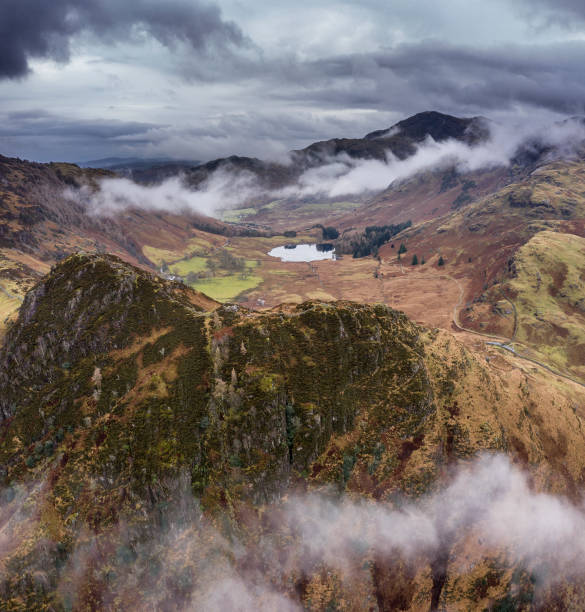 Aerial drone landscape image of Beautiful vibrant Winter sunrise over Blea Tarn in Lake District with snow capped Langdale Pikes in distance stock photo