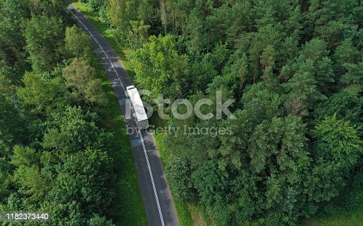 Aerial drone perspective view on white truck with cargo trailer riding through the forest on curved asphalt road.