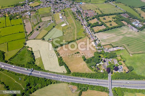 istock Aerial drone photo of the UK village of Cleckheaton in Bradford West Yorkshire in the UK showing farmers fields along side the M63 Motorway in a bright sunny summers day 1244503310