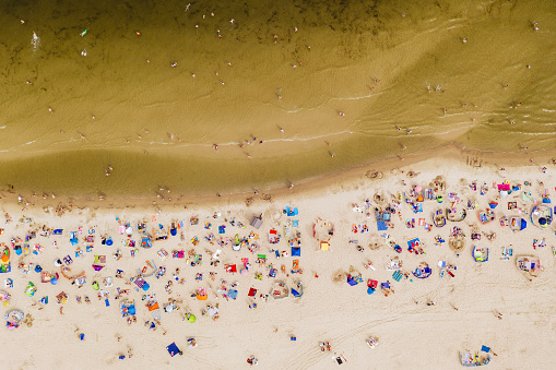 Aerial drone photography of the crowd of people on the beach.