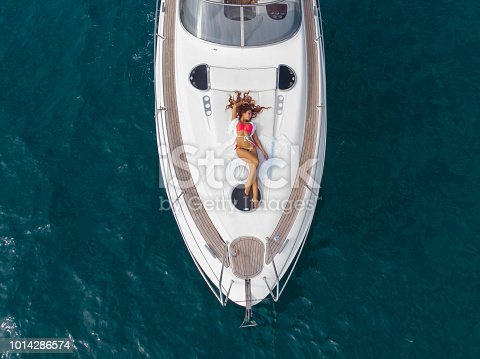 Aerial flight with drone DJI over amazing Girls sunbathing Luxury Lifestyle Sailing Boat Healthy Outdoor Living Freedom Travel Tourism. Girls sunbathing. Girl with long hair enjoying a cruise on a yacht.