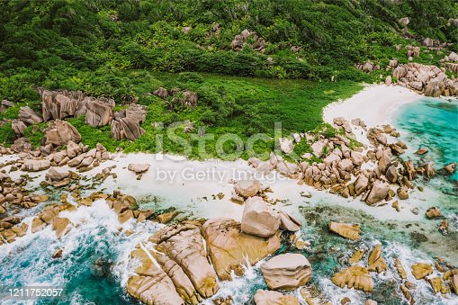 Aerial drone shot of Seychelles tropical remote secret beach Marron at La Digue island. White sand beach with turquoise ocean water and orange granite rocks.