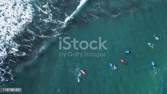 Aerial view of surfer swimming on board near huge blue ocean wave in Porto da Cruz, Madeira island, Portugal