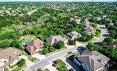 Aerial drone view above suburb homes in Cedar Park , Texas green Texas Hill Country landscape with large luxury homes and houses rooftops view high above landscape suburbs all the way to horizon