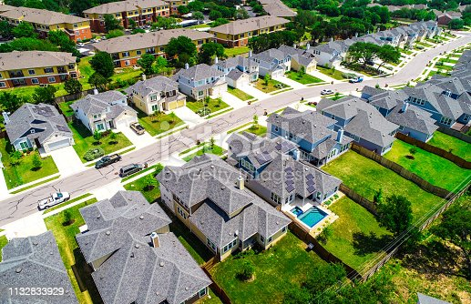 istock Aerial drone view above suburb rooftops in long line of new homes 1132833929