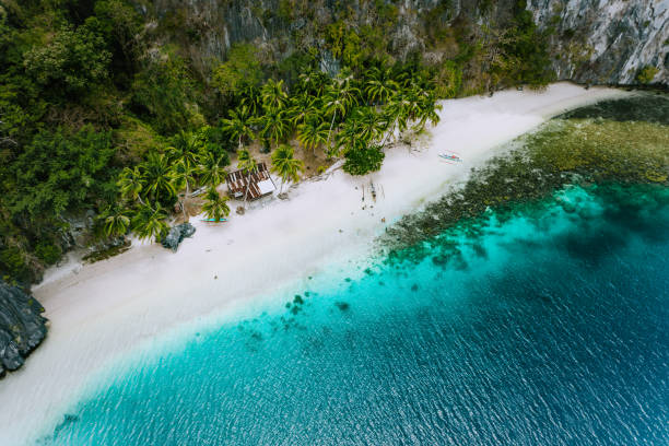 Aerial drone view of abandoned house hut on Pinagbuyutan Island in El Nido. Amazing white sand beach and emerald lagoon water Aerial drone view of abandoned house hut on Pinagbuyutan Island in El Nido. Amazing white sand beach and emerald lagoon water. pinagbuyutan island stock pictures, royalty-free photos & images