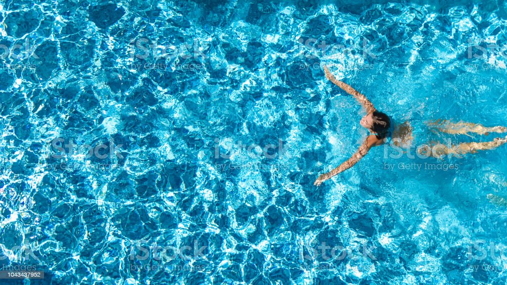 Aerial drone view of active girl in swimming pool from - Swimming pool girl christmas vacation ...