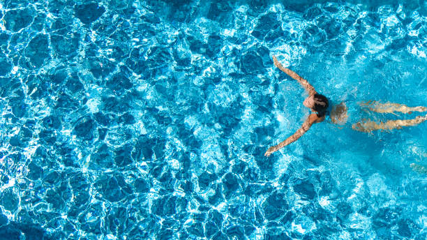 Aerial drone view of active girl in swimming pool from above, yong woman swims in blue water, tropical vacation, holiday on resort concept Aerial drone view of active girl in swimming pool from above, yong woman swims in blue water, tropical vacation, holiday on resort concept swimming pool stock pictures, royalty-free photos & images