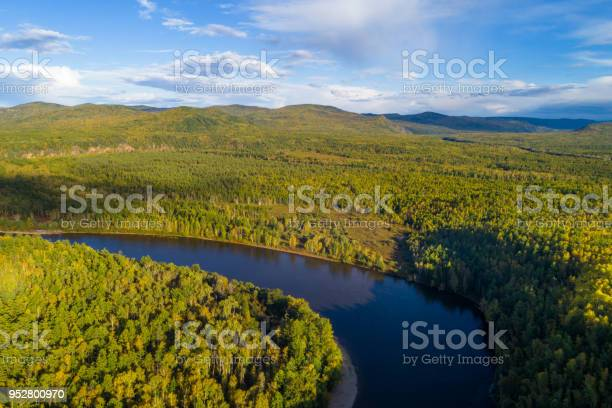 Photo of Aerial drone View of autumn mountains and small river with forests in sunrise soft light. Majestic landscape.
