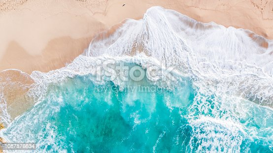 Aerial drone overhead view of huge beach and dynamic sandy, rocky coastline with large crashing foamy waves over turquoise water.