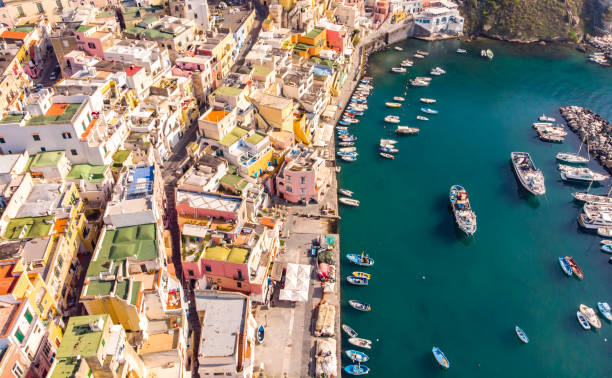 aerial drone view of corricella fisherman village in procida island naples italy - procida foto e immagini stock