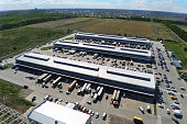 Aerial drone view of group of large modern industrial warehouse or factory buildings in suburban city area.Logistic transportation cargo terminal.