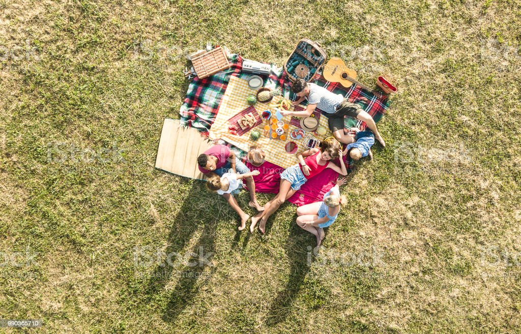 Aerial drone view of happy families having fun with kids at picnic barbecue party - Multiracial happiness and love concept with mixed race people playing with children at park - Warm bright filter stock photo