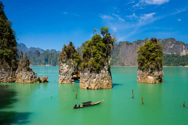 정글로 둘러싸인 거대한 호수에서 장엄한 석회암 손가락과 카르스트 주변의 롱테일 보트의 공중 드론 보기 - 카르스트 지형 뉴스 사진 이미지